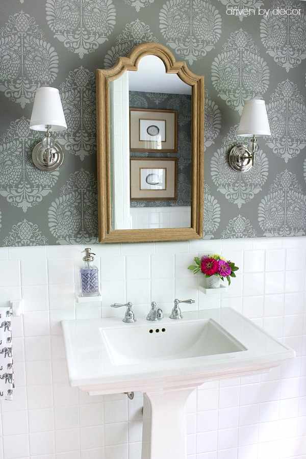 Stenciled bathroom walls, twin scones flanking medicine cabinet and pedestal sink