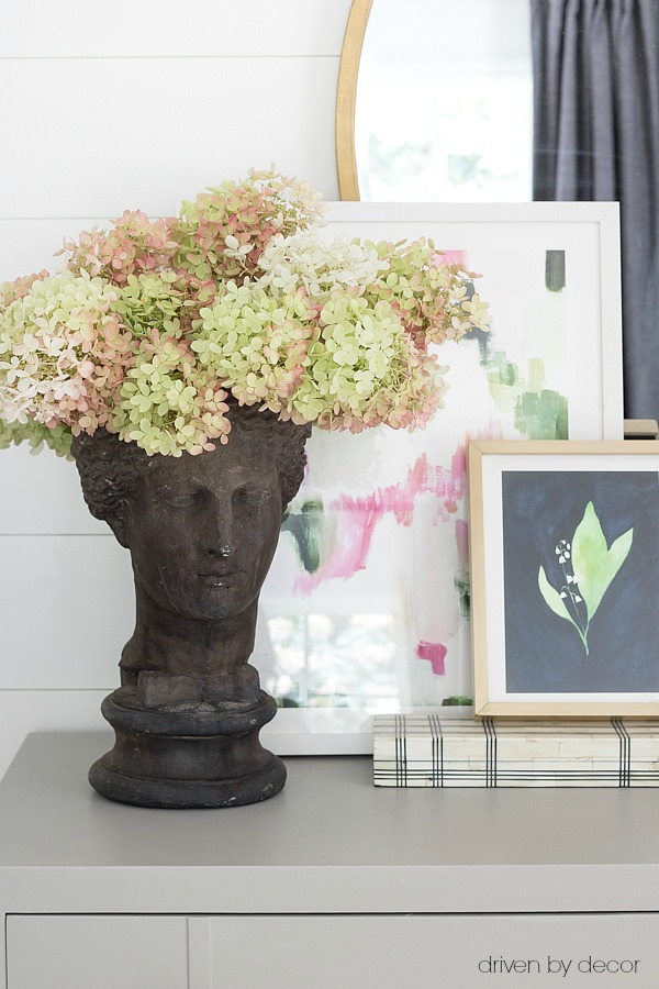 Unique planter filled with hydrangeas and layered art on dresser