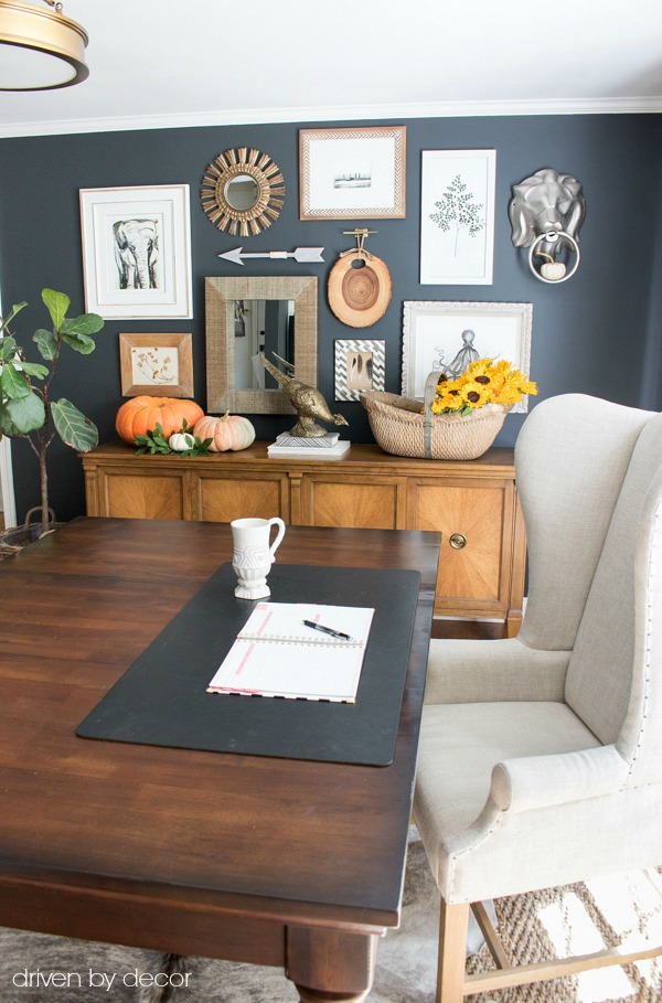 Wingback chair, office desk, and console with gallery wall decorated for fall