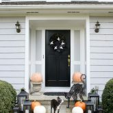 Front porch Halloween decorations - pumpkins in urns, lantern trios, and spooky cat