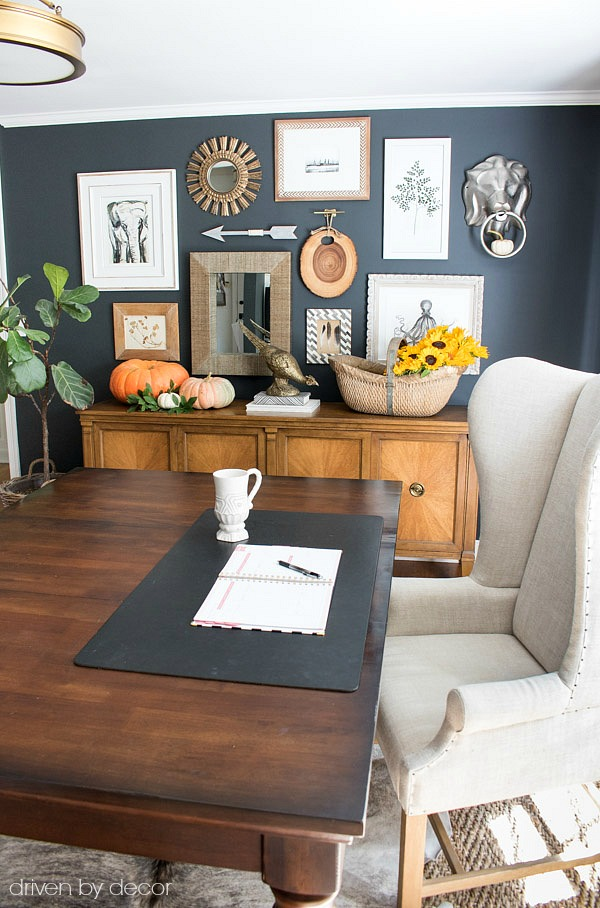 Home office with wingback desk chair and eclectic gallery wall above console