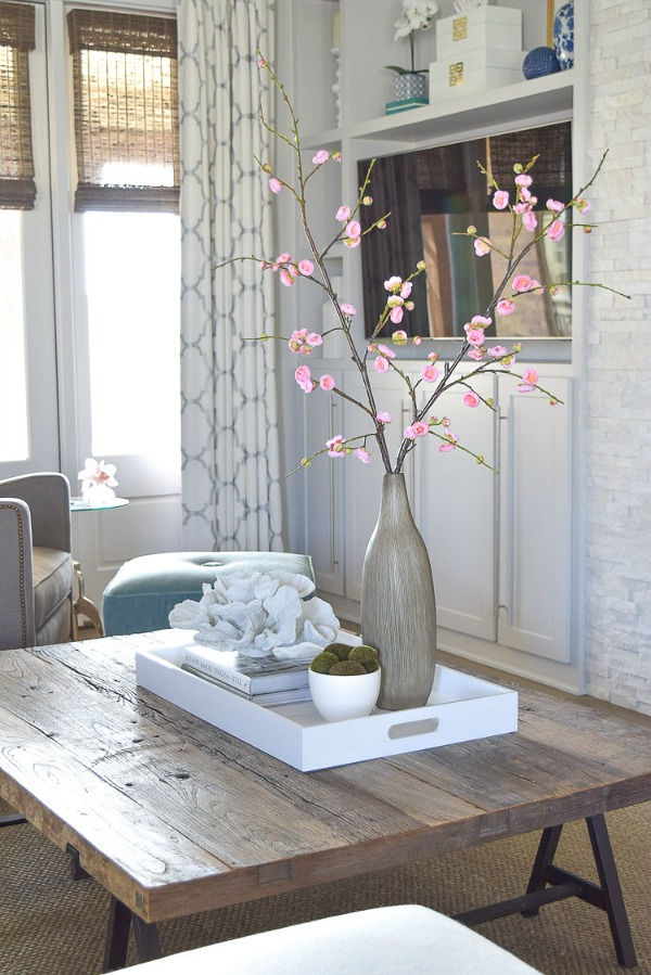 One coffee table styling tip is to incorporate natural elements like coral or plants
