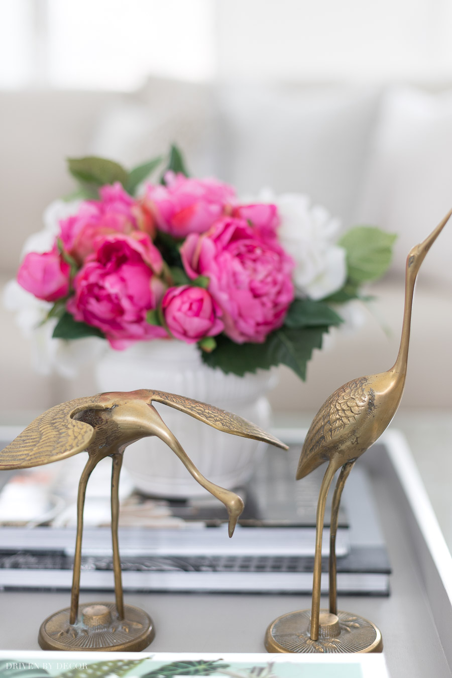 A pair of vintage brass cranes used as coffee table decor