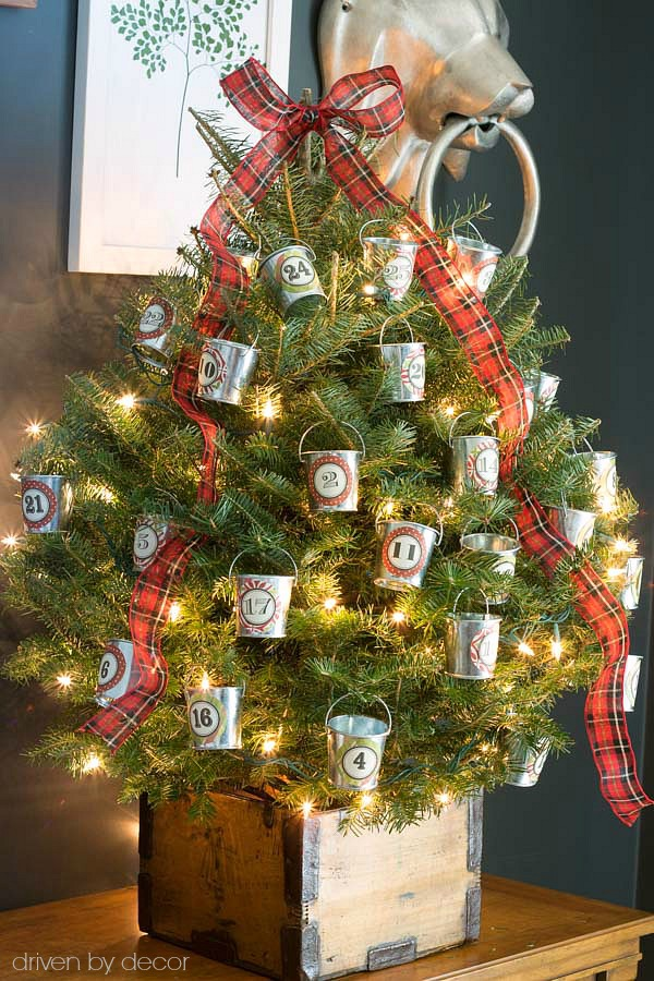 A mini Christmas tree turned advent calendar by adding daily treats to numbered mini galvanized buckets