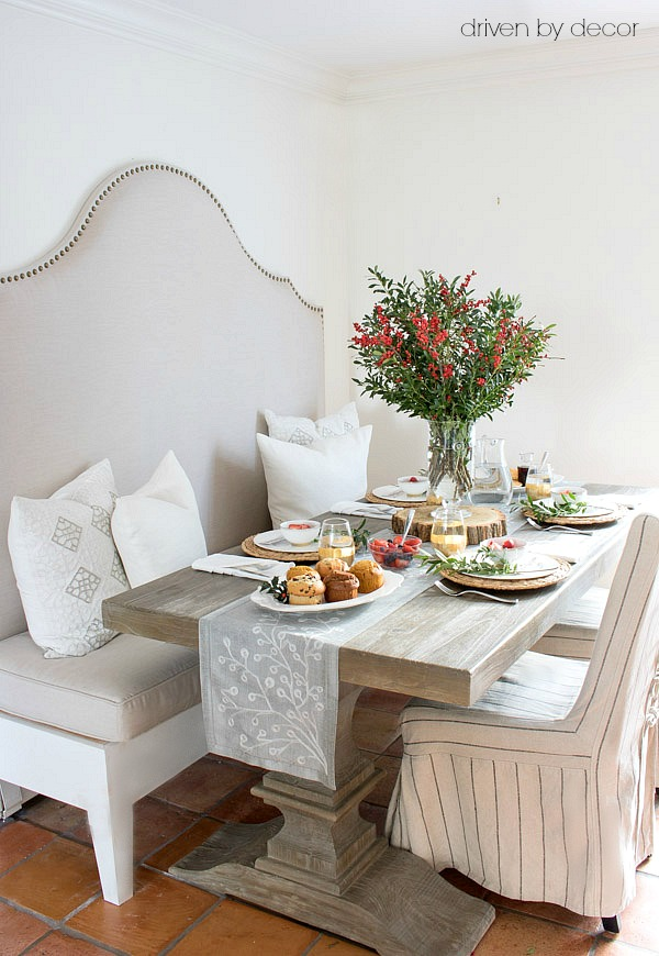 DIY upholstered banquette with reclaimed wood pedestal table and slipcovered chairs