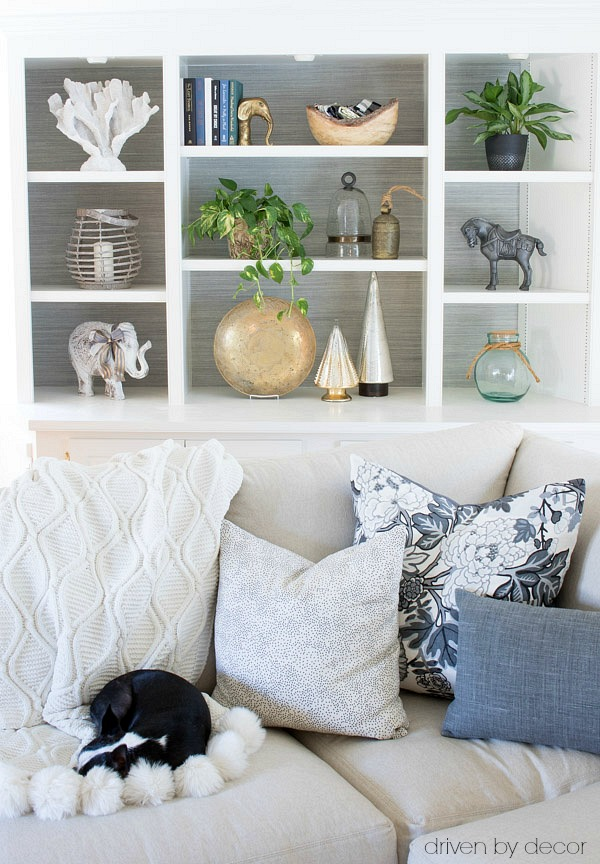 Bookcase backed in grasslcoth adn sectional with neutral pillows and cozy pom pom throw