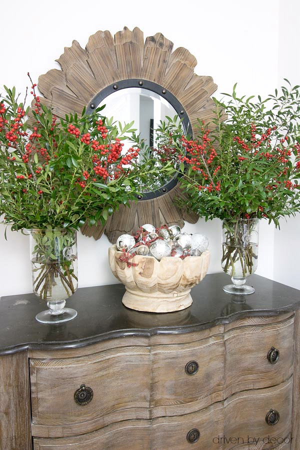 Christmas home tour - a bowl full of ornaments flanked by vases of boxwood branches and berries for entryway Christmas decor