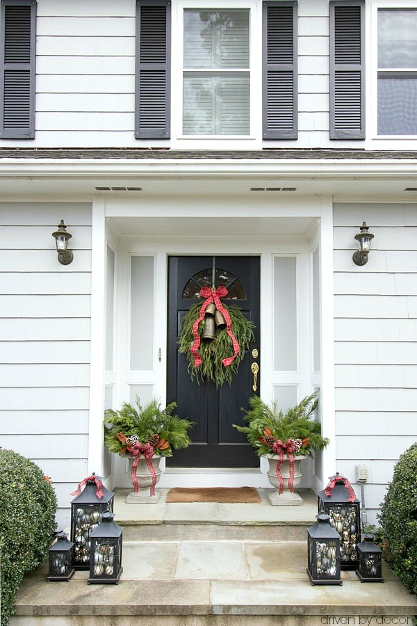 Christmas house tour - a trio of lanterns filled with ornaments, planters filled with greenery, and a greenery swag on the front door are simple porch decorations for Christmas
