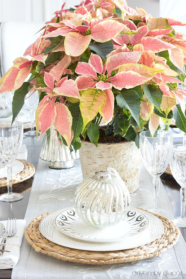 An oversized ornament adorns each plate on this Christmas tablescape
