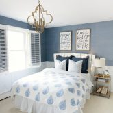 Blue and white bedroom with grasscloth wallpaper, quatrefoil pendant, and paisley bedding