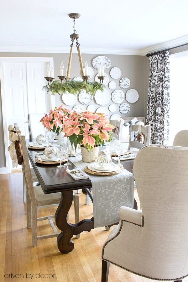 Christmas home tour - dining room decorated with pink poinsettias and gold and silver ornaments and decorative trees. Simple and beautiful!