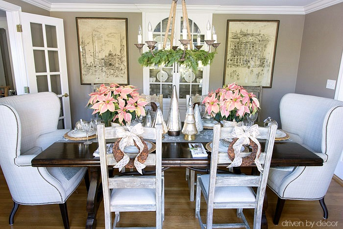 Christmas home tour - dining room table decorated for Christmas with a mix of silver and gold and pink poinsettias