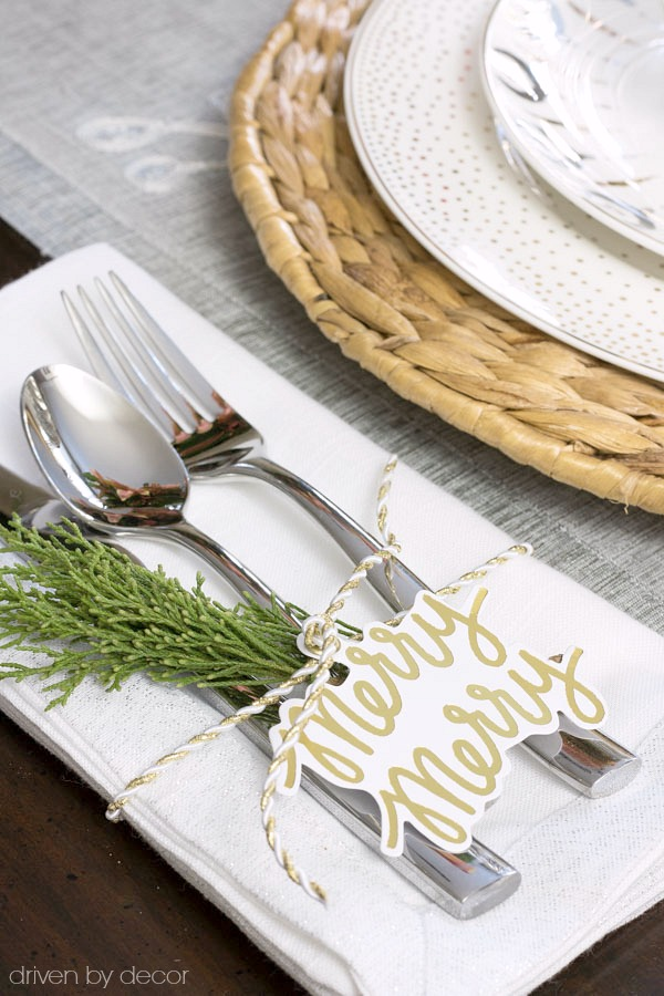 Holiday gift tags and a sprig of greenery adorn this simple Christmas placesetting