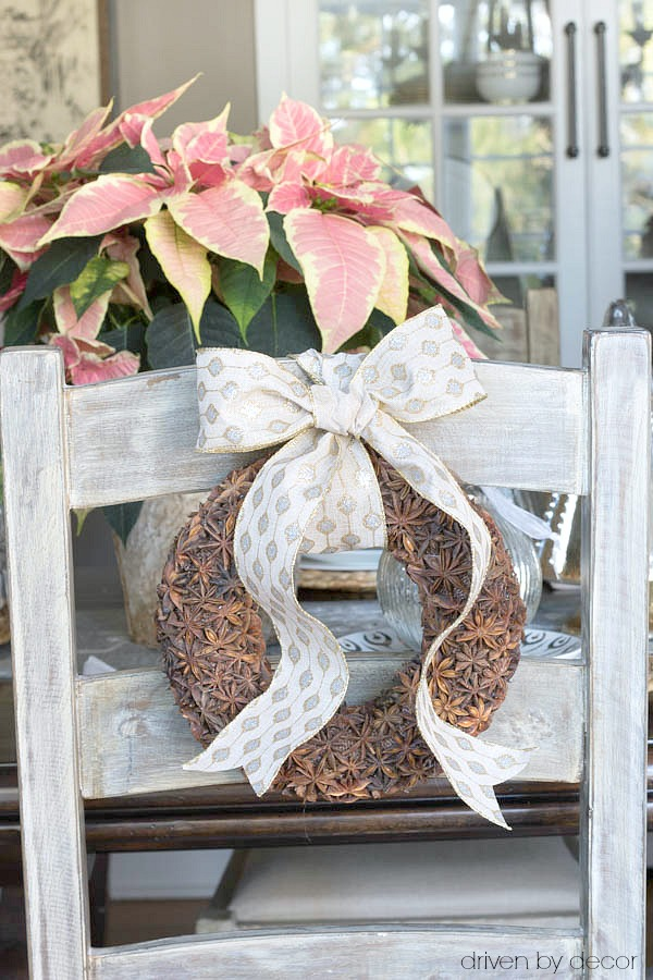 Small star anise wreaths tied to ladderback chairs for Christmas