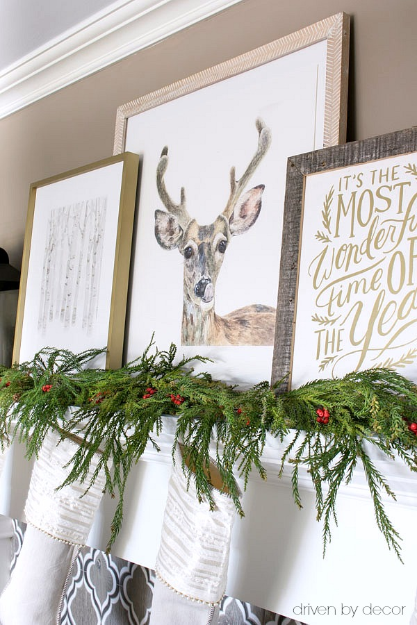 A trio of art prints layered on this pretty Christmas mantel
