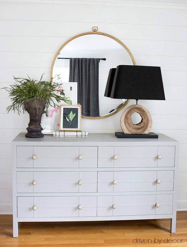 Gray painted dresser with simple styling of a large round mirror, layered art, and greenery-filled planter head