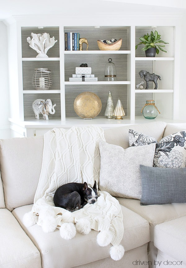 Bookcases lined in grasscloth wallpaper and cozy pom pom throw add texture to this newly made-over family room