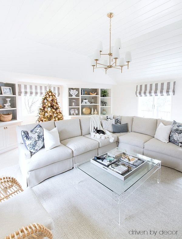 Christmas house tour of neutral living room with vaulted planked ceilings, a slipcovered sectional, acrylic coffee table, and more!