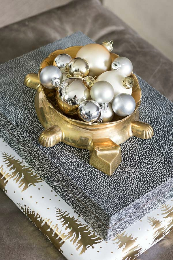 Simple silver and gold Christmas ornaments in a fun bowl to decorate for the holidays