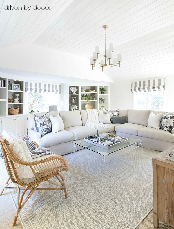 "Family room makeover - a HUGE change from the ""before""! Includes slipcovered sectional, rattan chair, tiered brass chandelier, acrylic coffee table, and vaulted shiplap ceiling"