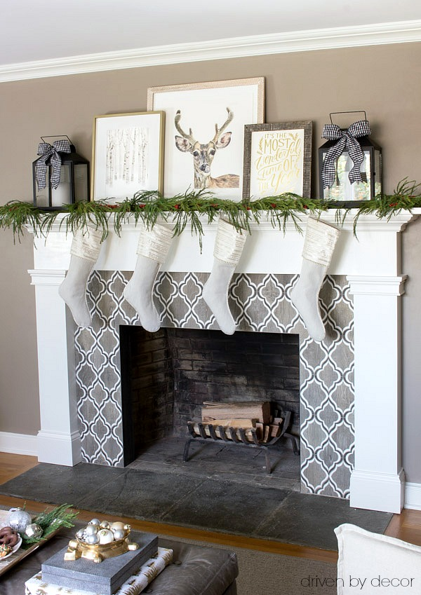 Holiday art prints, lanterns, and greenery used to decorate the mantel for Christmas