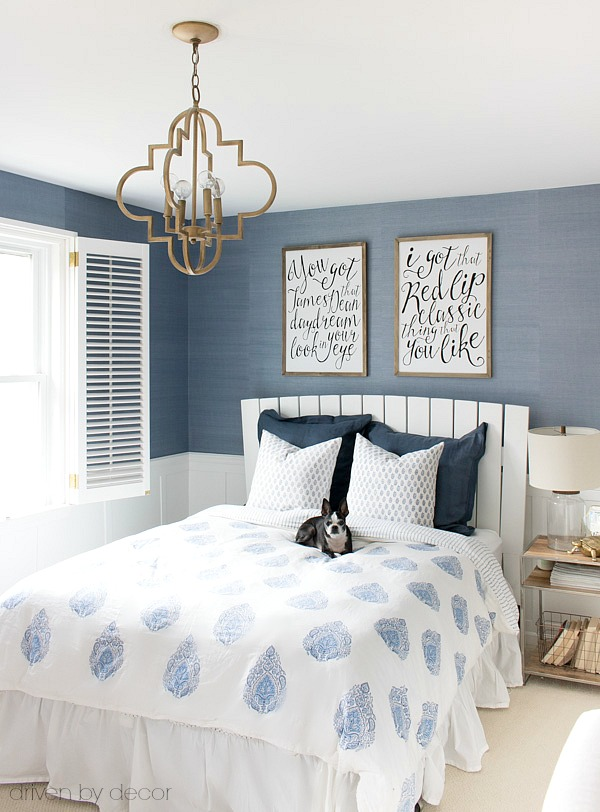 A classic white slatted headboard allows the grasscloth wallpaper and gorgeous blue and white bedding to shine!
