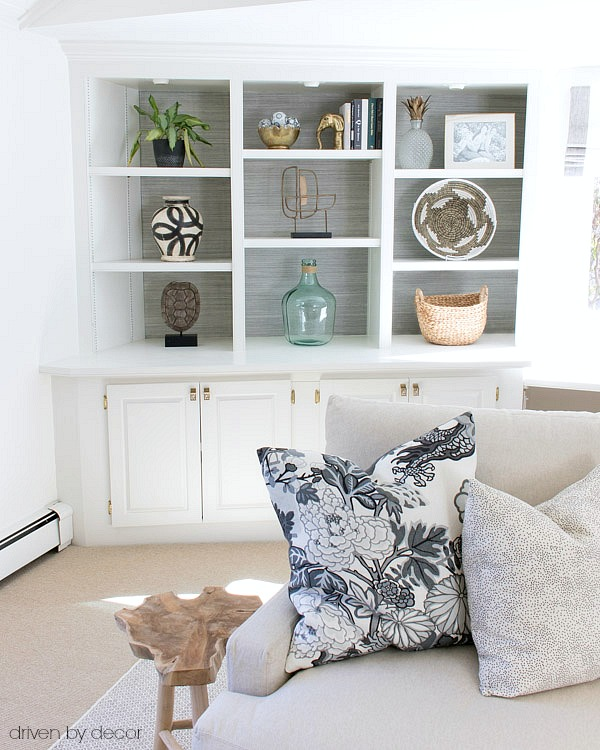 Love the simple bookcase styling and textured grasscloth lining the back