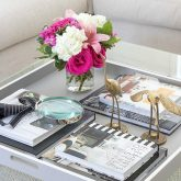 Coffee table with simple styling of a tray with books, brass cranes, a magnifying glass, and flowers