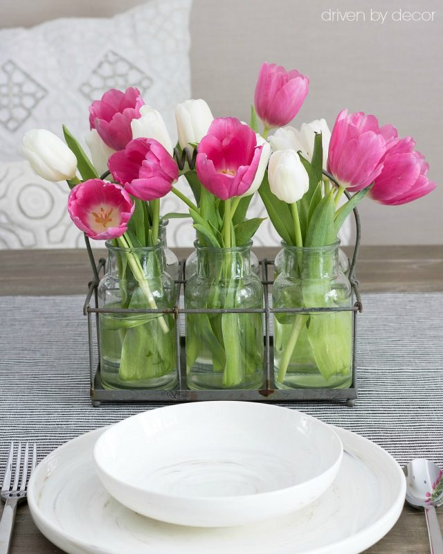 Pink and white tulips in milk bottle vases