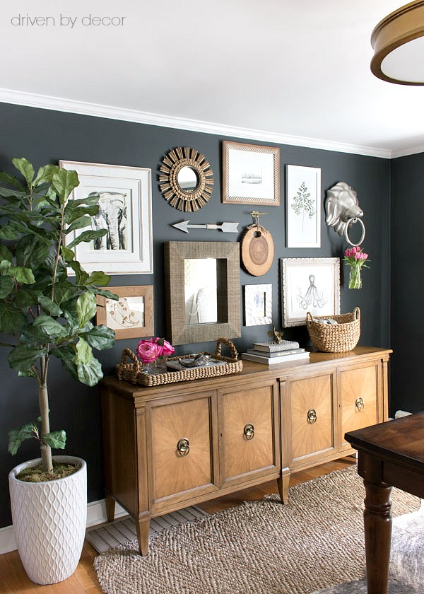 Great gallery wall arrangement with art prints and mirrors above a vintage console