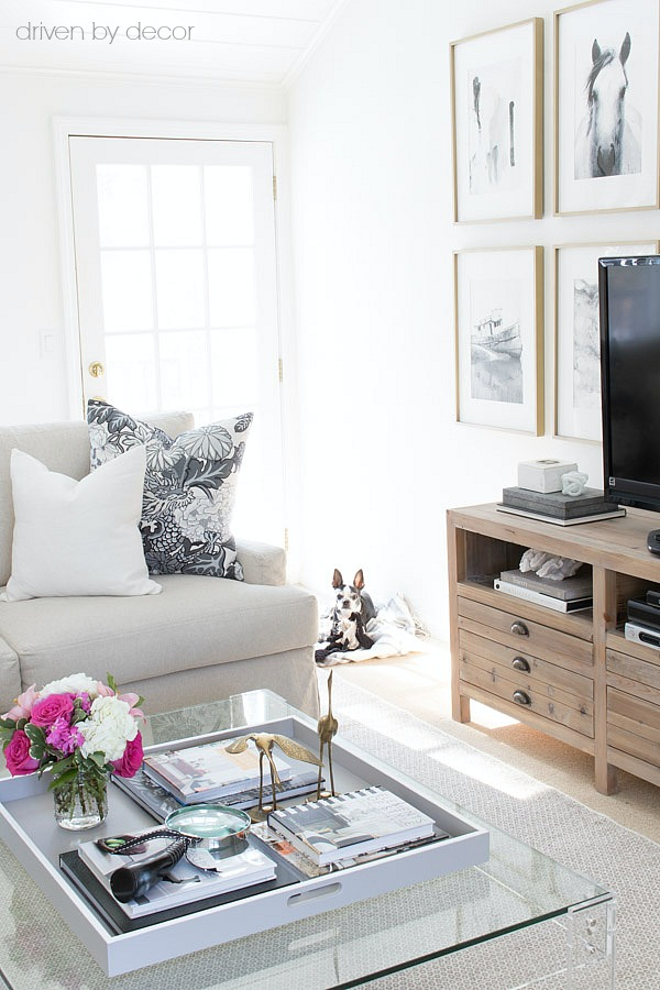 Acrylic coffee table with large painted tray, wood console, slipcovered sectional, and art wall