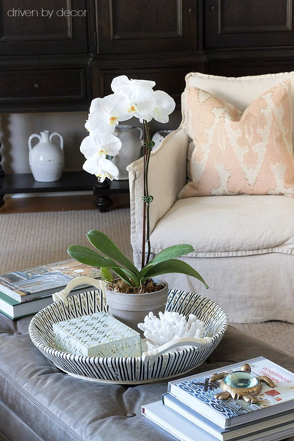 How to style a rectangular coffee table - a round tray with flowers, a decorative box, and coral with stacks of books on each side