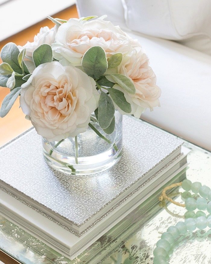 A vase of faux flowers is part of this simple side table styling