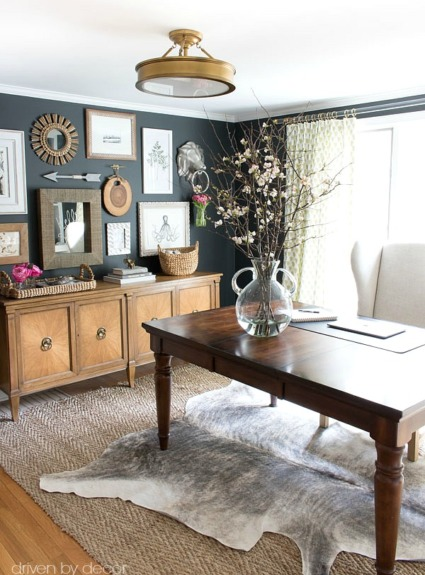 Home office with layered rugs (jute and cowhide) and eclectic art gallery against charcoal walls
