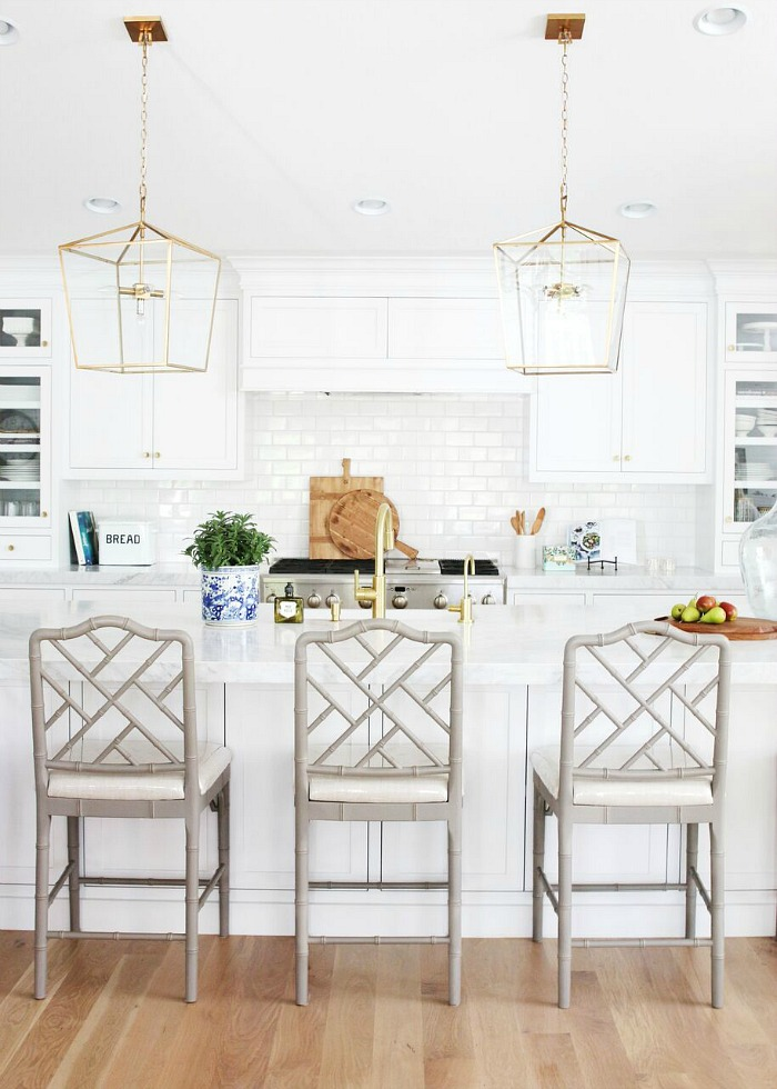White kitchen with open brass pendants over the island and gray lattice backed counter stools - Studio McGee