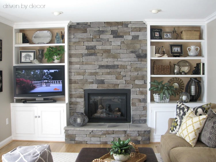 Family room with stone fireplace flanked by built-in bookcases