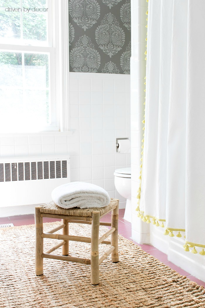 A small woven stool from HomeGoods is perfect for keeping a towel outside of the shower