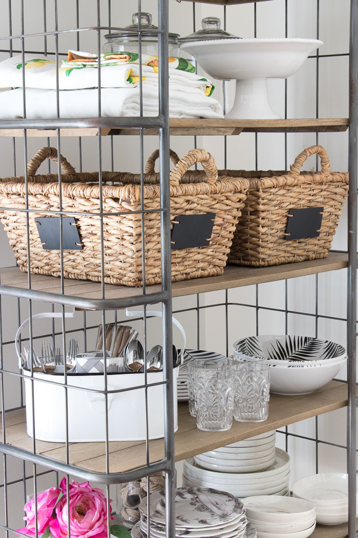 Summer entertaining essentials stored on a wire baker's rack by a door to the patio