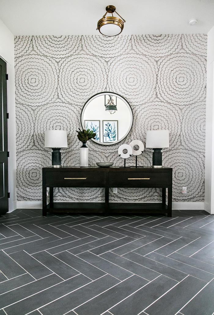 Stunning entry designed by Sita Montgomery Interiors with black herringbone floors and a long console with twin lamps and a round mirror.