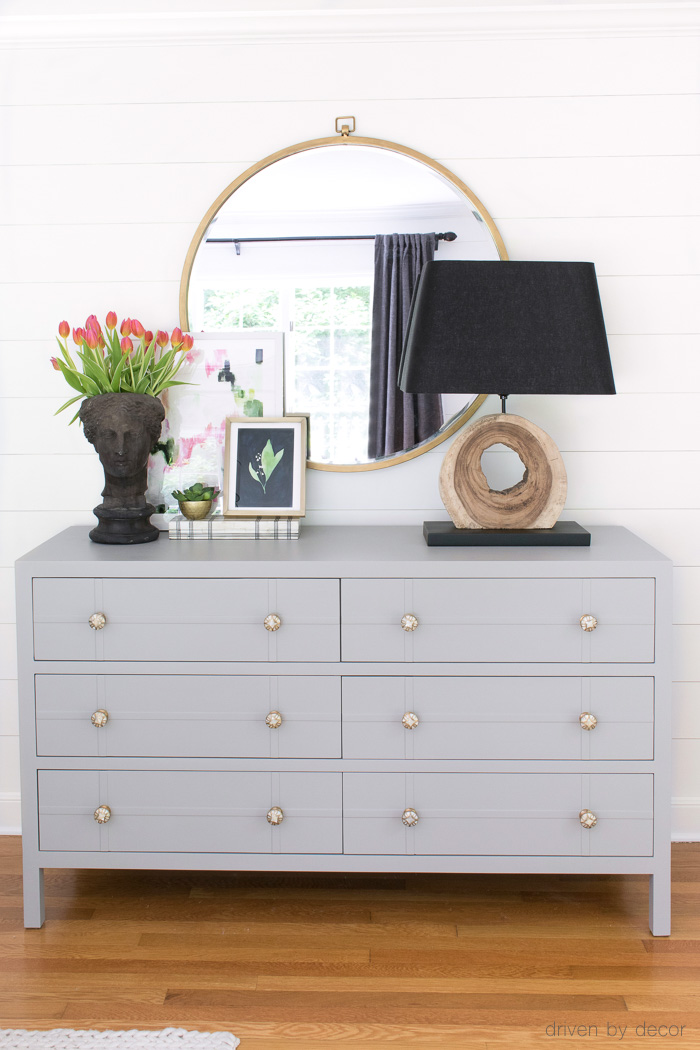 Painted bedroom dresser with round mirror, wood lamp, planter head, and layered art!