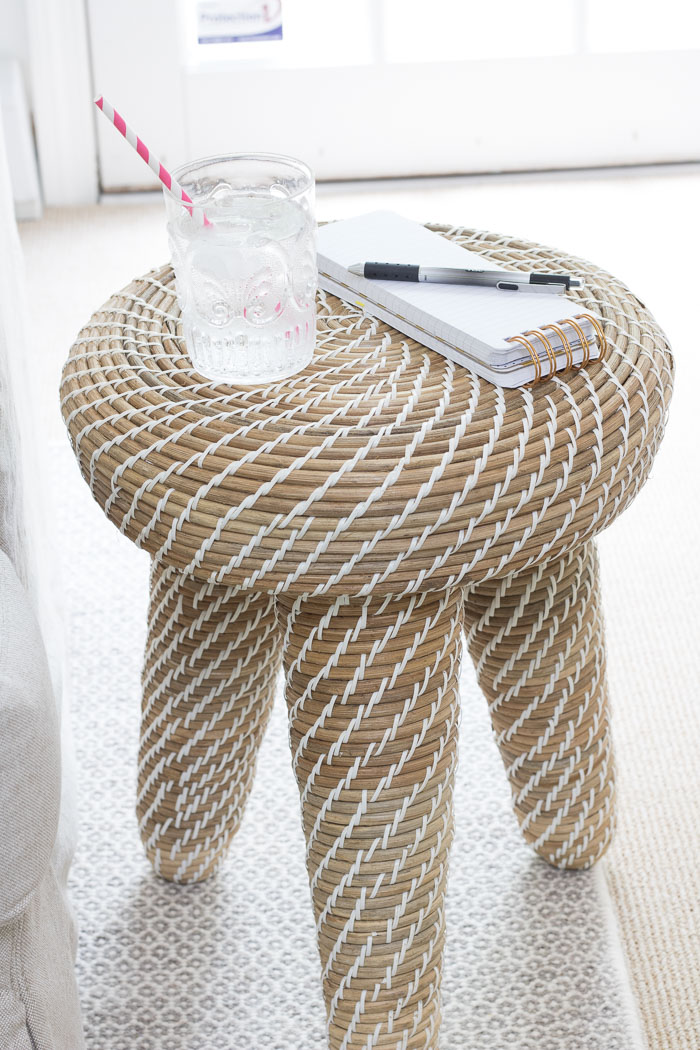 Small woven side table that adds a beachy, casual vibe to this family room!