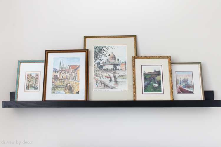 When arranging art on a ledge shelf, overlapping framed prints creates a more cohesive look!