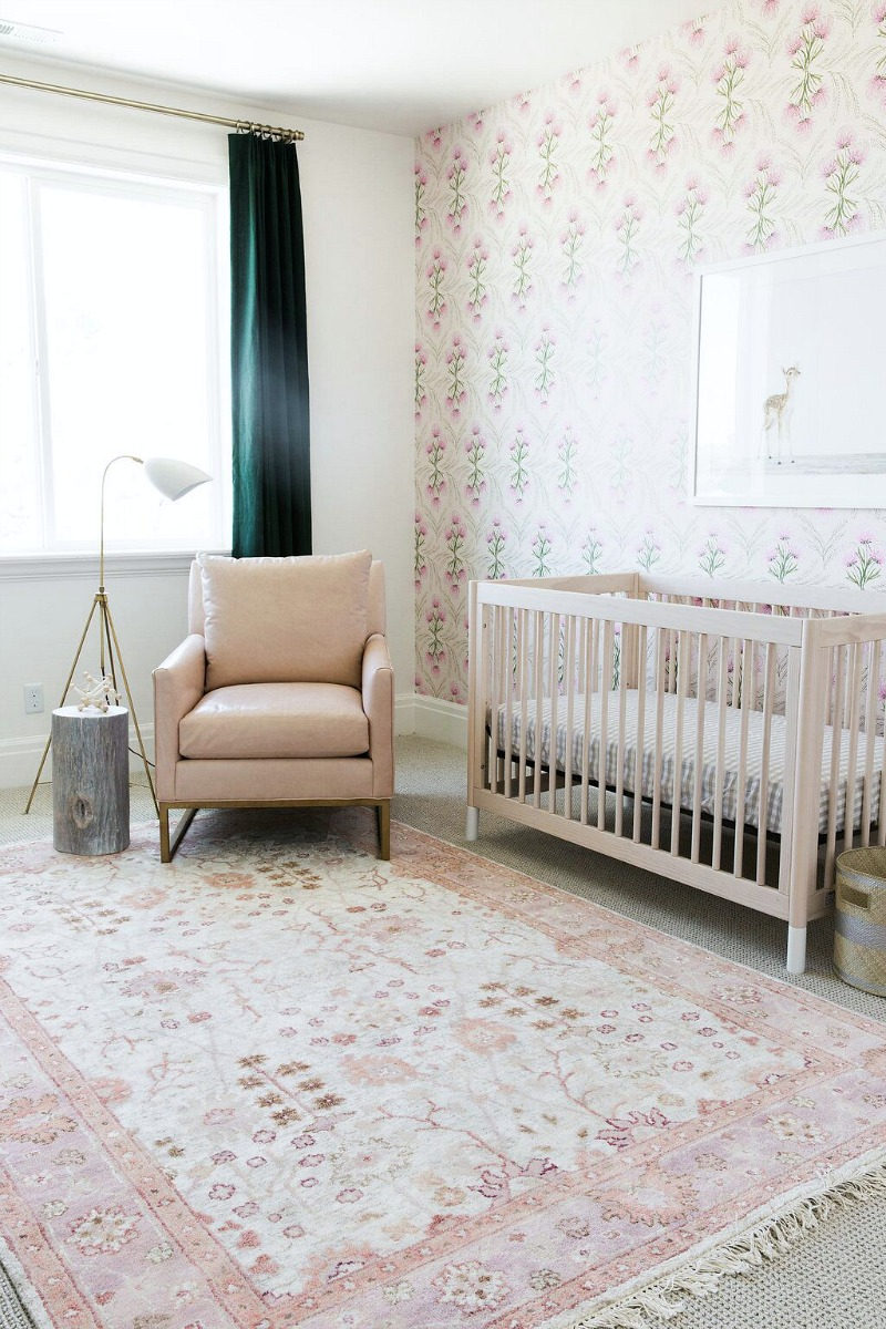 Beautiful baby's room with gorgeous pink patterned rug and focal wall with wallpaper