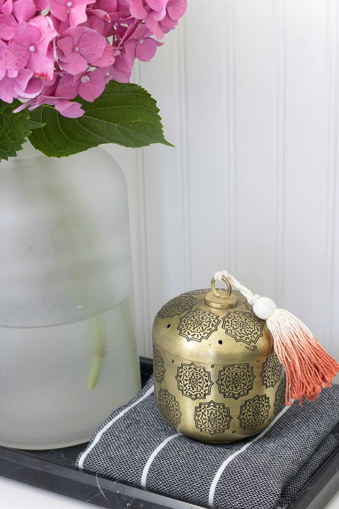 A tasseled brass vessel to hold Q-tips and cotton balls for guests - great toilet tank decor :)