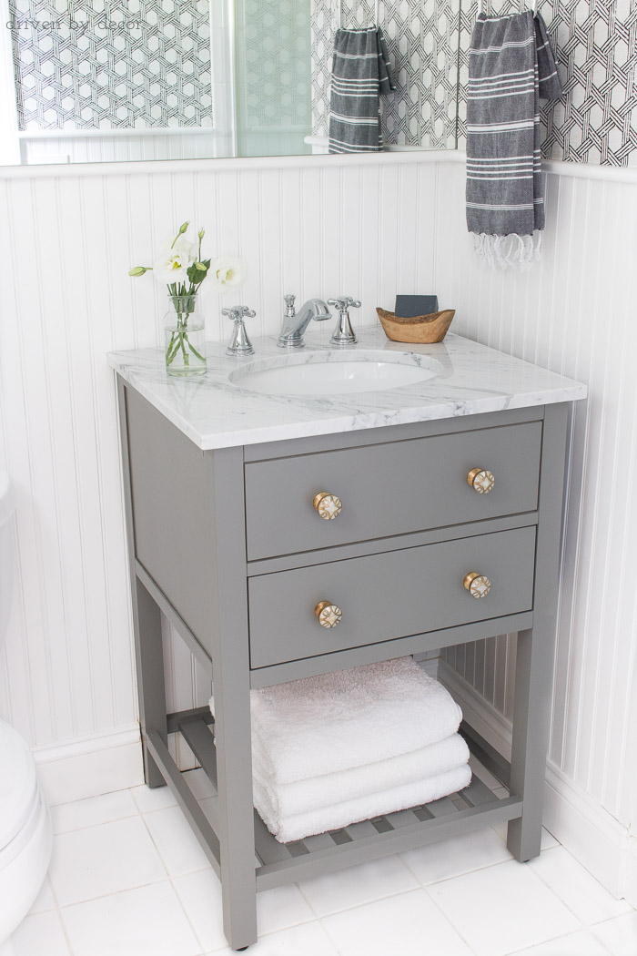 Small space single sink gray vanity with white marble top and classic Delta Cassidy bathroom faucet - links to everything in post!