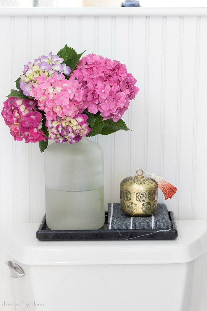 A black marble toilet tray is perfect for corralling a few accessories on top of the toilet tank!