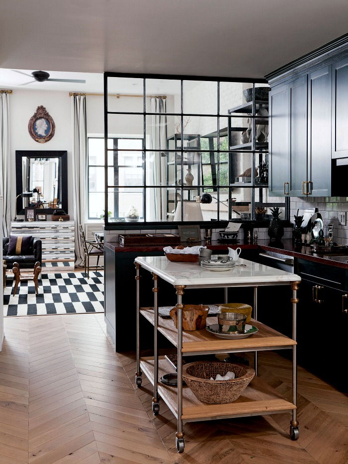 Gorgeous kitchen with freestanding marble island, herringbone wood floors, and dark cabinetry