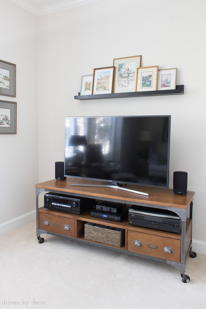 Love this solution for the bare wall above your flat screen TV! Art is on a ledge shelf so can be swapped in and out easily!