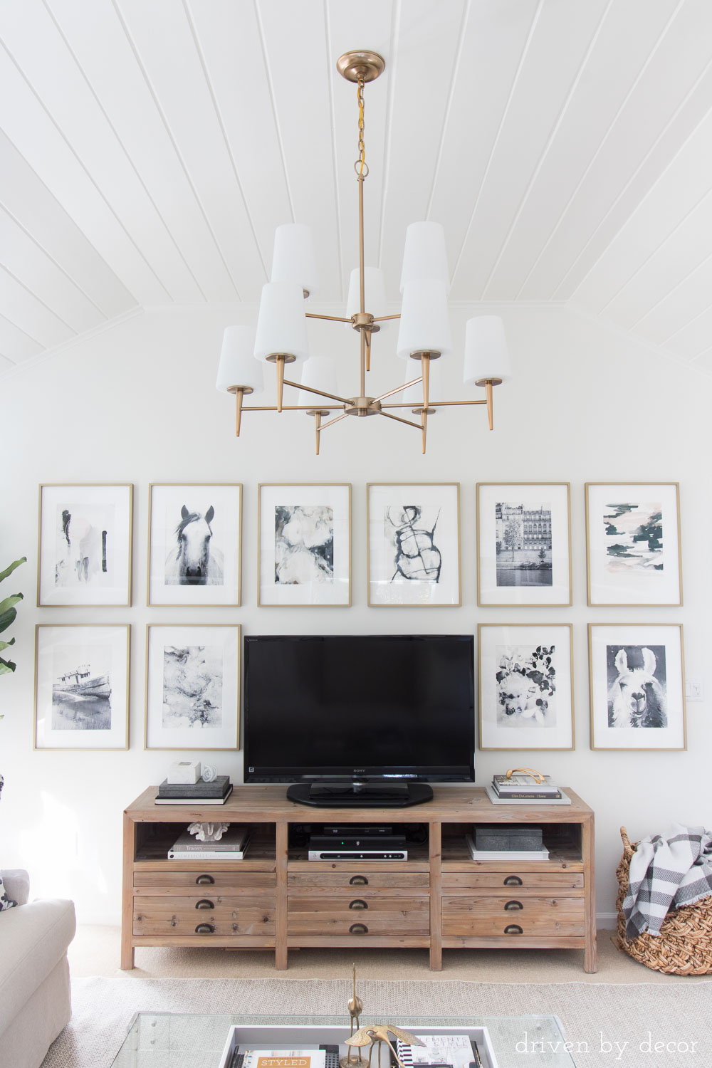 Love the art hung around the TV and that statement chandelier and wood media console!