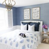 Blue and white bedroom with grasscloth walls, hand blocked duvet, and gold pendant chandelier